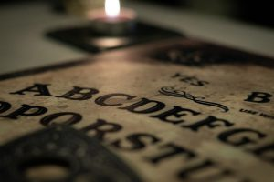 Een Ouijabord in het donker met een kaars