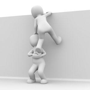Life Coach helpt persoon over een muur